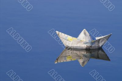 a paper boat floating in a lake