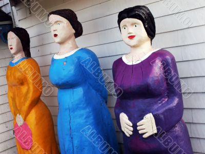 Three female statues in bright clothing