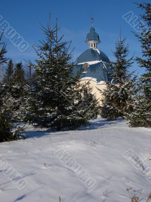 Winter snowy landscape with fur-trees and church