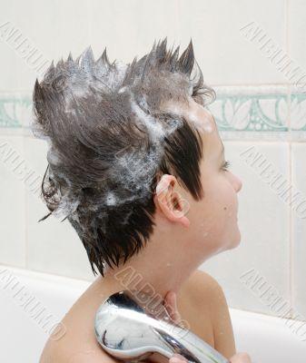 Boy with hair in soap in bathtub