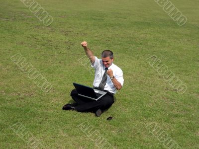 Happy man with computer in the field