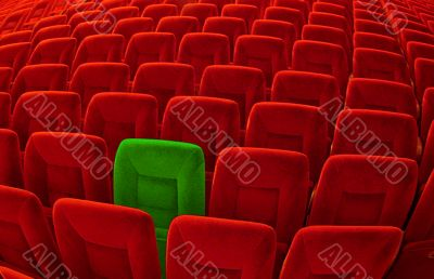 One green chair among many red seatings
