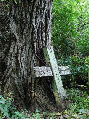 Aged broken wooden cross near huge wood