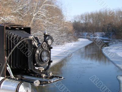 Ancient photo camera shoting snowy riverside
