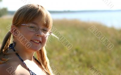 A merry girl is spectacled near a sea