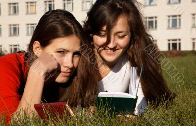 Girls reading the books on the lawn