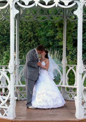 Wedding Pair Kissing in White Summer House