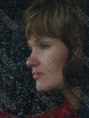 Girl looks thru waterdropped widow glass