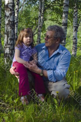 Grandfather and granddaughter in the woods