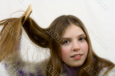 Portrait of the young girl combing hair
