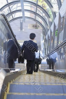 Businessman on moving staircase