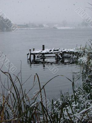 First season snowfall on riverside water