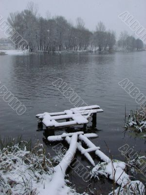 First season snowfall on riverside water