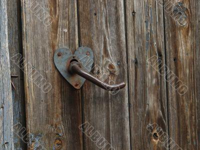 Aged door handle on wooden door