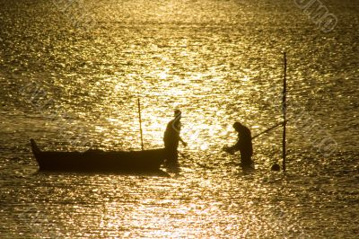 Two fisherman in water with back light