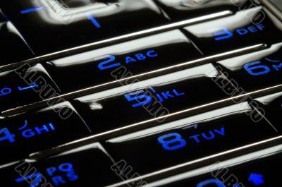 Blue mobile keypad under dark