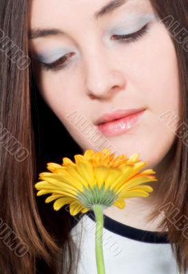 beautiful girl smelling yellow daisy