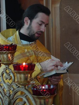 orthodox priest praying with Gospel in hands