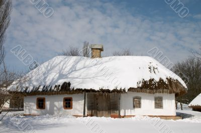 Peasant`s house under snow