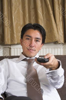 business man on a sofa with remote control