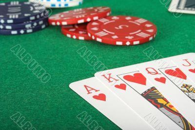 casino tokens and a royal flush over green