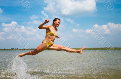 girl jumping above the lake