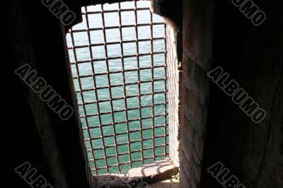 Grilled castle window overlooking the sea