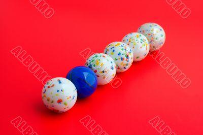 One blue ball amongst five white balls