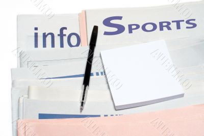 Note and pen, over stacked sports newspapers