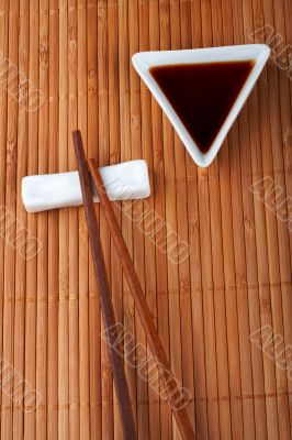 A pair of asian chopsticks and soy sauce