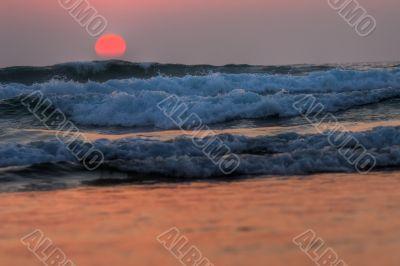 red sunset on waves, atlantic coast