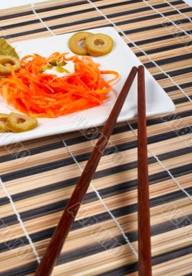Salad of carrot on a porcelain plate with sticks