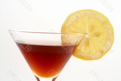 Detail of red cocktail with lemon