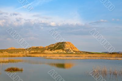 Hill over the blue sky and the lake