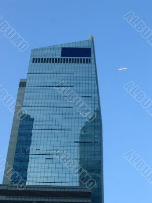 Corporate building with a plane on the blue sky