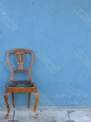 wooden chair alone with blue background
