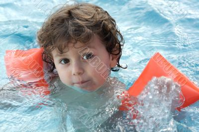 adorable boy learning to swim