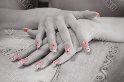 two hands with painted and decorated nails