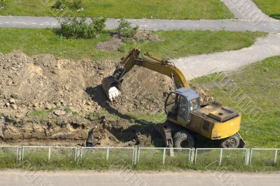 Excavator and man are digging together