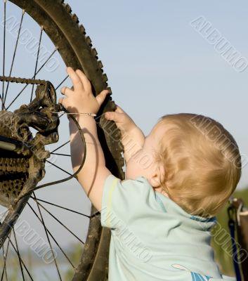 Child playing with bike wheel