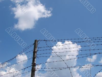Cloudy blue sky with rugged wire fence