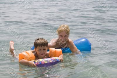 Smiling Boy and mom swimming in the ocean