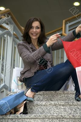 The young beautiful woman with purchases in stor