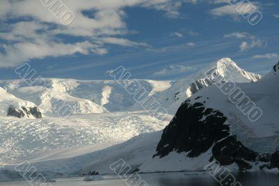 Polar twilight: Glaciated mountains with cloudy blue sky