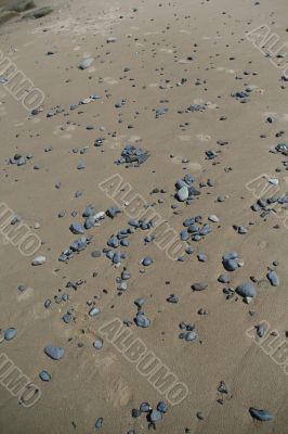 Rounded pebbles scattered along sandy beach