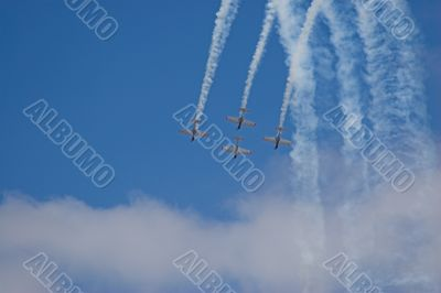 four planes in formation with vapour trails