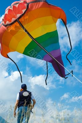 man plays with big colorful fish kite