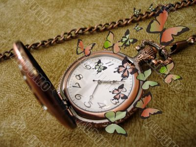 old golden clock on vintage background with many green butterfli