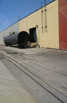 Black tank car, on railroad siding