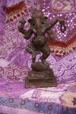 Bronze Ganesha dancing, on purple